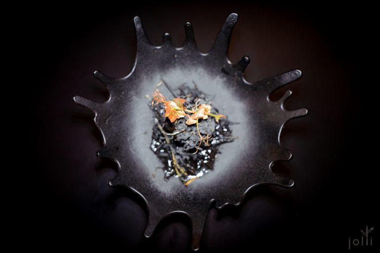 黑色盘子,装着黑色食物,还有古铜色的叶枝点缀