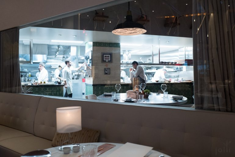 隔着玻璃看到厨房及主厨餐桌