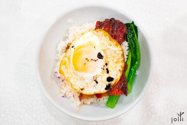 一大碗白饭上有两大件叉烧、一只荷包蛋、两条菜