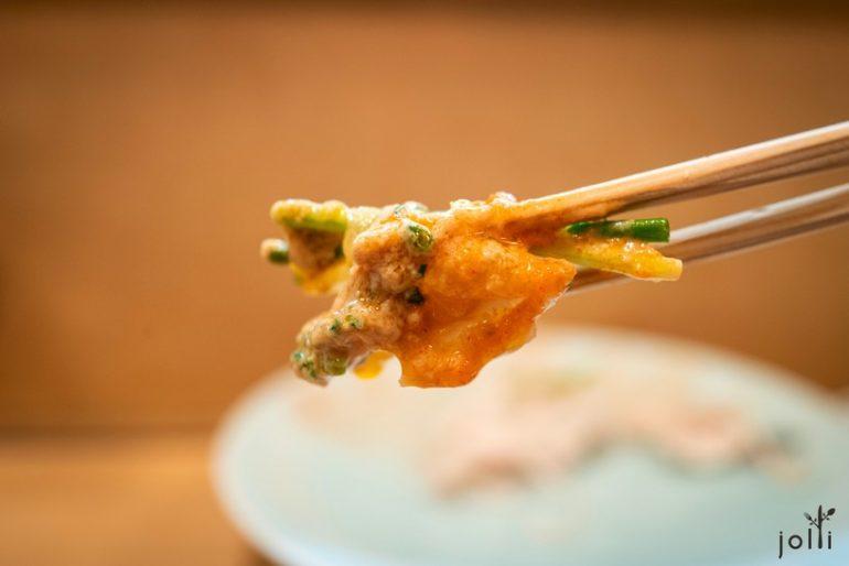 河豚生魚片裹著淺蔥及河豚皮,掛上安康魚肝紅葉泥醬汁