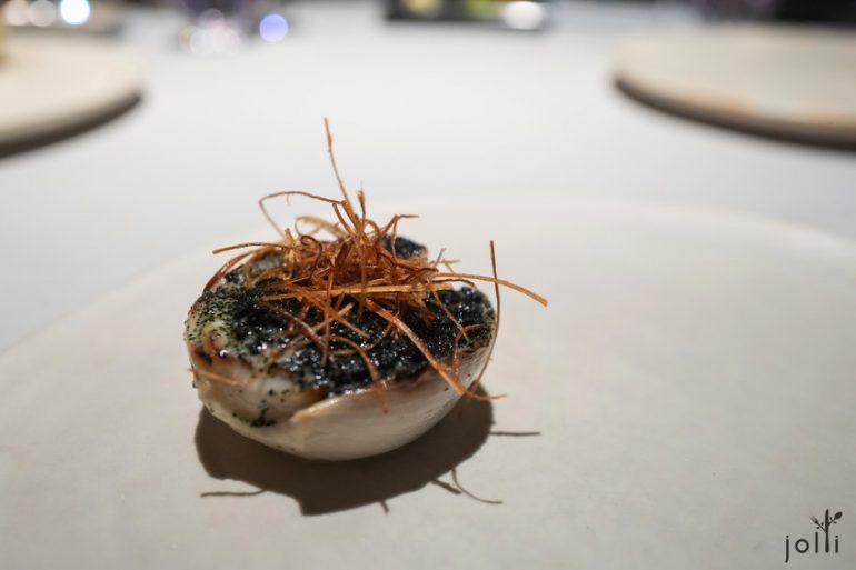 渍烤洋葱配鱼子酱、海藻粉与乳液及烤韭葱