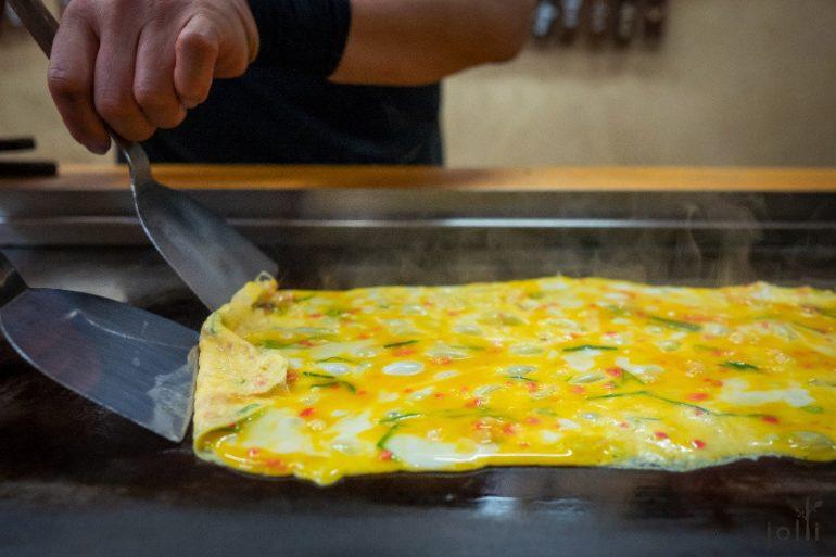 将蛋浆混入葱花及红姜碎,然后铺开在铁板上