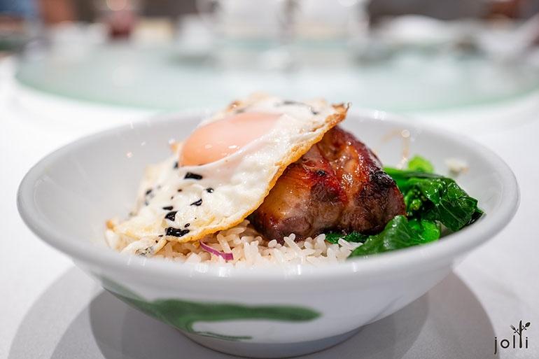 一大碗白飯上有兩大件叉燒、一隻荷包蛋、兩條菜